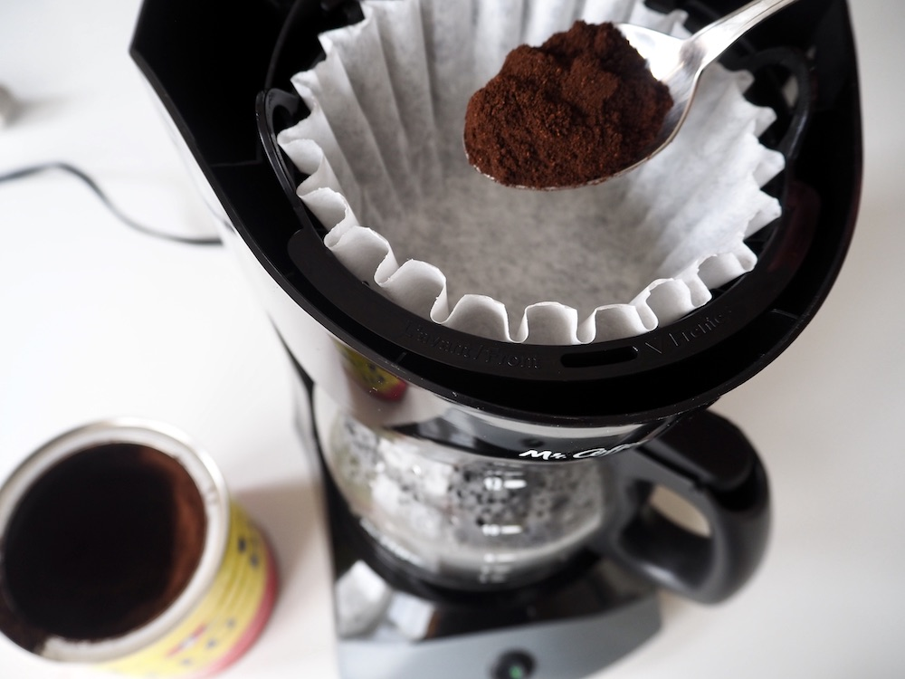 Person putting espresso grounds into a drip coffee maker