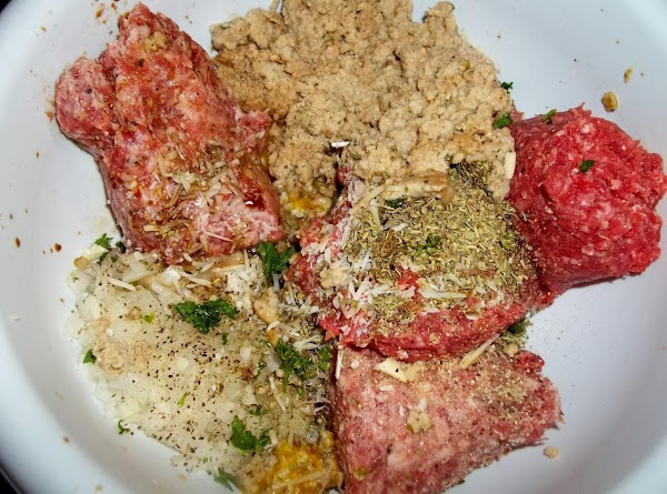 In large bowl, combine the meats,cheese, bread crumbs soaked in milk,onion, eggs, garlic, parsley.salt...
