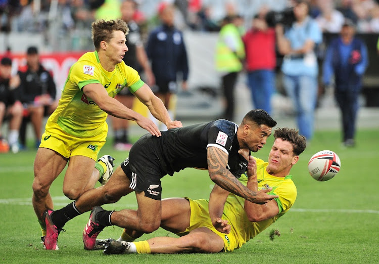 Matthew Hood of Australia (l) and teammate Simon Kennewell of Australia (r) combine to tackle Regan Ware of New Zealand during day 1 of the 2017 HSBC Cape Town Sevens at Cape Town Stadium on 9 December 2017.
