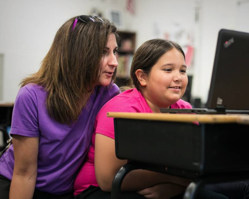 A teacher is looking at a Chromebook screen with a young female student.