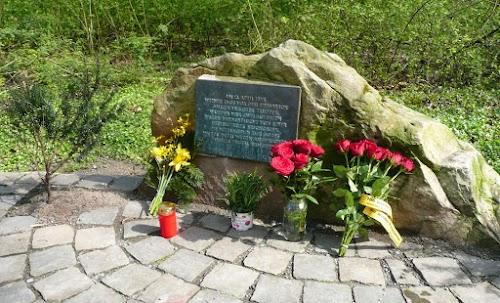 Blumenschmuck am Gedenkstein mit -tafel: »Am 12. April 1945, wenige Tage vor dem Einmarsch amerikanischer Truppen, wurden hier zwei Soldaten wegen Fahnenflucht von einer Heeresstreife erschossen. Die Mitbürgerin Else Gores wurde dabei wegen angeblicher Beihilfe brutal ermordet.«.