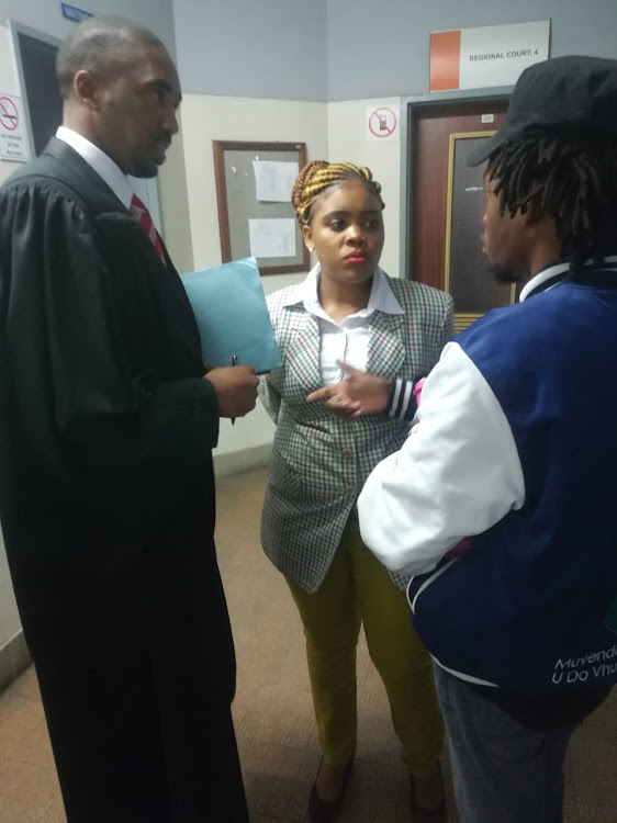 Sibongile Mani, who is a Pan Africanist Student Movement of Azania secretary at the Walter Sisulu University, gets instructions from her lawyer Asanda Pakade at court in East London while #OutsourcingMust#Fall and Pasma leader Vusi Mahlangu looks on.