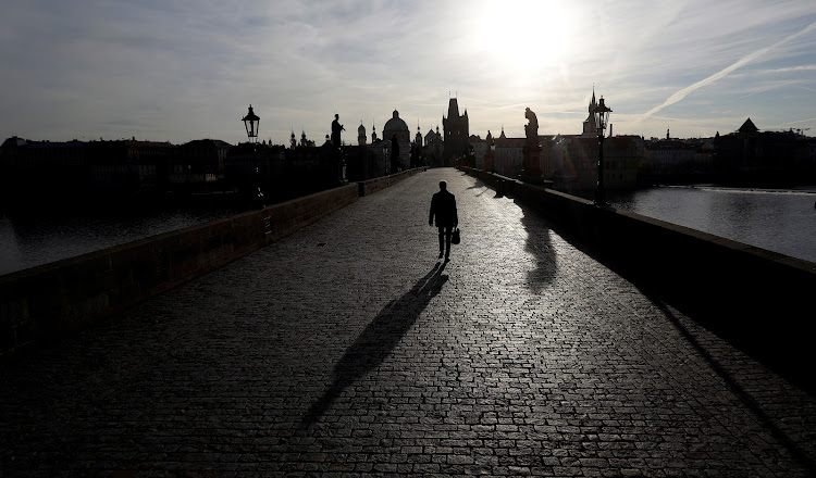 A man walks across the empty medieval Charles Bridge in Prague, on March 16 2020, as the Czech government restricts movement of people to slow the spread of the novel coronavirus.