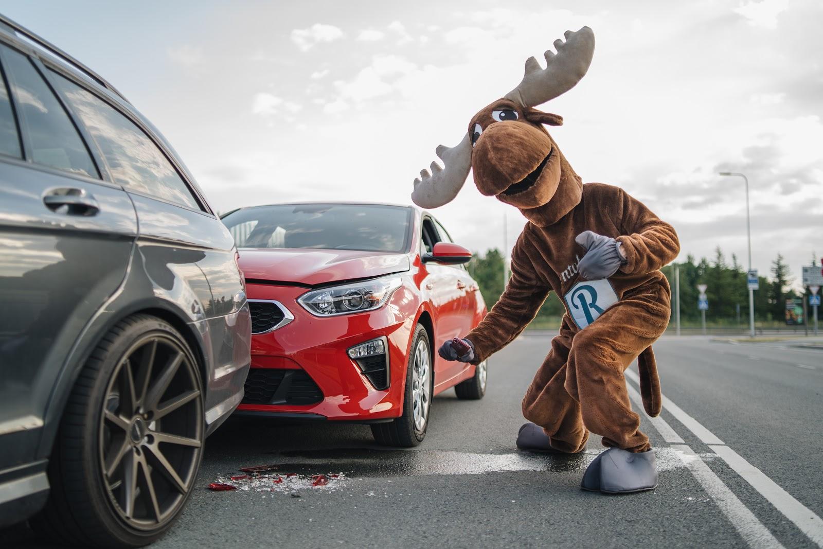 Rental Moose mascot photographs damaged red Kia Rental car. Make sure to gather proof if you crash a rental car.