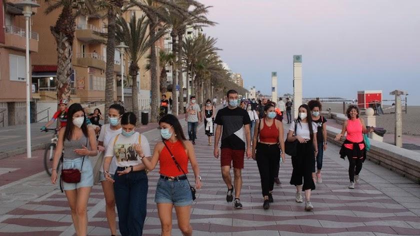 Almerienses con mascarillas en el Paseo Marítimo de Almería.