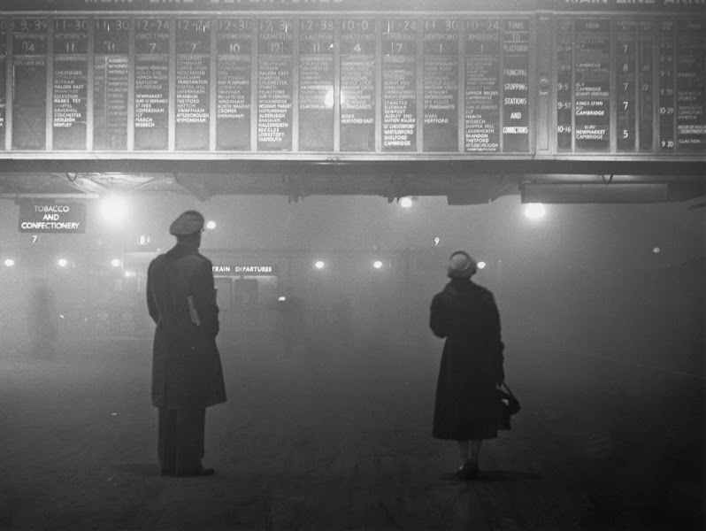 Photo: Two passengers looking at the train departure board at Liverpool Street Station, London, during heavy fog, 29th January 1959. Most rail services have been delayed because of the weather. (Photo by Edward Miller/Keystone/Hulton Archive/Getty Images)