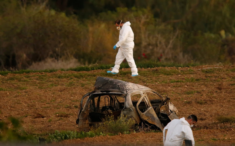 Forensic experts walk in a field after a powerful bomb blew up a car (Foreground) and killed investigative journalist Daphne Caruana Galizia in Bidnija, Malta, October 16, 2017.