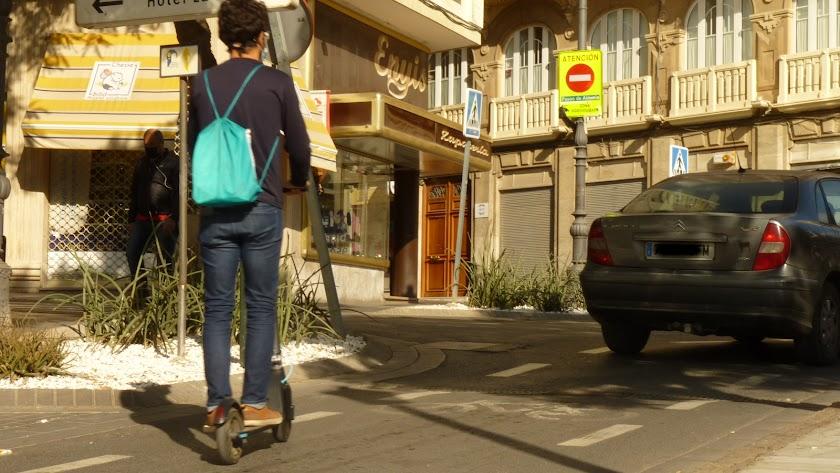 Usuario de un patinete eléctrico por el centro de la ciudad