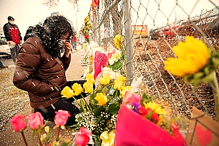 Slide 1 of 21: Stephanie Kaiser becomes emotional as she places flowers at the site of a mass shooting at King Soopers grocery store in Boulder, Colorado, March 23, 2021. REUTERS/Alyson McClaran