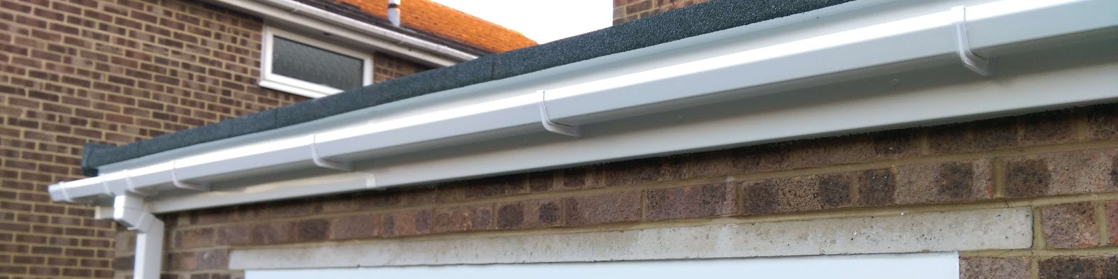 a newly installed gutter on facebrick home