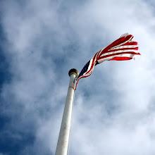 Photo: America Flag against clouded sky