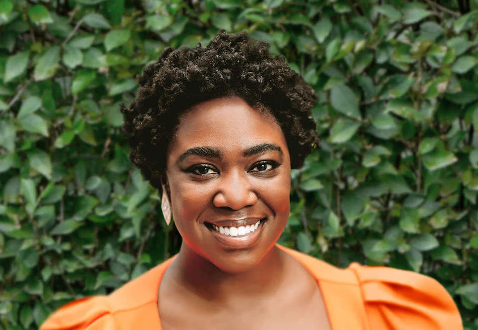 Tia McLaurin smiling in orange shirt with green foliage in the background