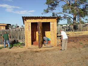 Photo: Outhouses in rural areas in Russia are something natural. This one has 2 separate rooms with 2 holes above the 1 main shit pit. A guy in green t-short accidentally dropped his brand new point- and-shoot camera. Fortunately it was in a case. His friend in blue t–short found a long metal wire and bent its end as a hook. Now he is trying to fish for the camera. As he reported, it is hard to breath and dark.