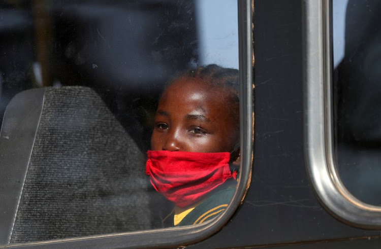 A girl wearing a face mask looks on through a bus window in Eikenhof, south of Johannesburg, as schools reopen during the Covid-19 lockdown in South Africa, on August 24 2020.