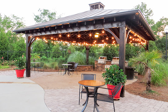 Poolside grilling pavilion with string lights, picnic tables, and two BBQ grills