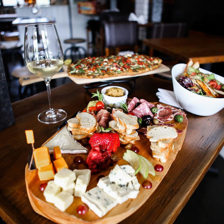 A cheese plate, flatbread, salad and glass of chardonnay. Photo: Palate Wine Bar and Market.