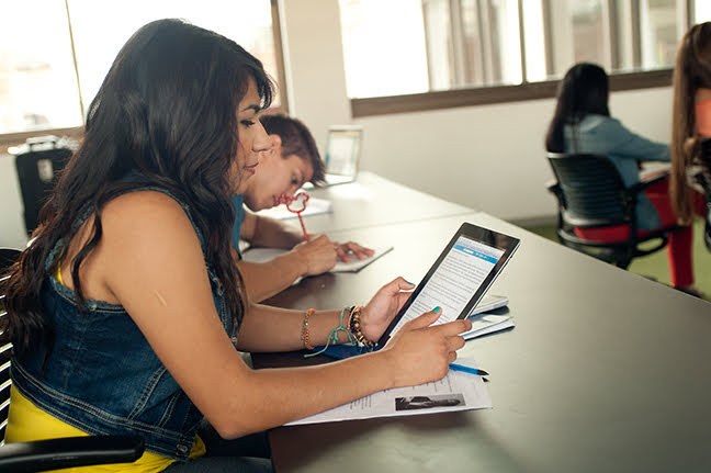 student looking at Web Reader on tablet in classroom