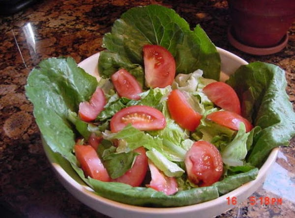 Make a simple salad of Romaine lettuce and sliced tomatoes and place in a...
