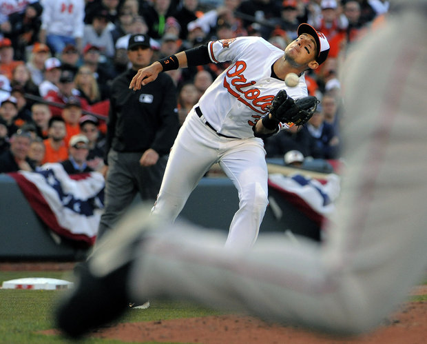 Orioles third baseman Ryan Flaherty twists his body to make a catch in the ninth inning against the Boston Red Sox.