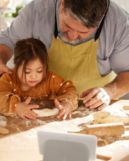 An overhead shot of the father's hands guiding his daughter as she learns to flatten dough with a rolling pin.