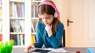 Una niña con auriculares mirando un tablet