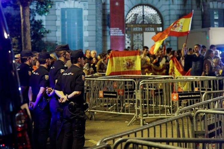 Spanish police officers stand guard as people hold Spanish flags during a gathering in favour of a unified Spain in Barcelona, Spain, on Wednesday. Picture: REUTERS