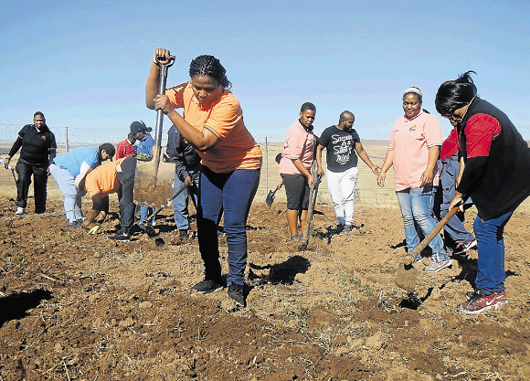 Eastern Cape provincial police commissioner Lieutenant-General Liziwe Ntshinga, centre, and fellow officers plant vegetables at the Tsolo Special School