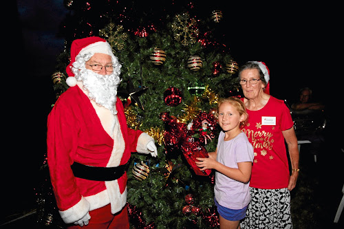 Aleira Sunderland lights up the CBD Christmas tree, pictured with Santa Claus and Narrabri Chamber of Commerce's Jenny Gale.