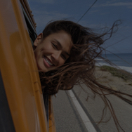 Woman smiling while leaning out car window, driving past the ocean
