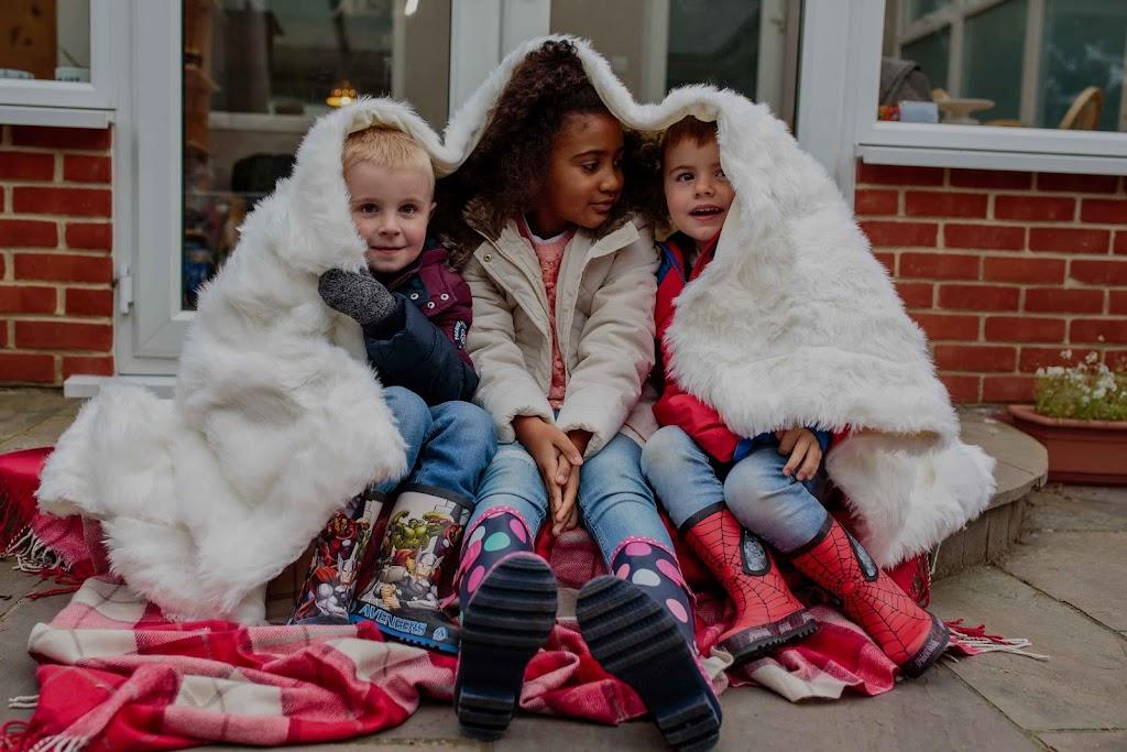 Three kids keeping warm under blanket outside