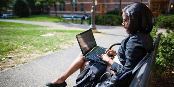 A woman on bench using a laptop