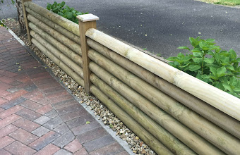 a wooden fence next way to a driveway