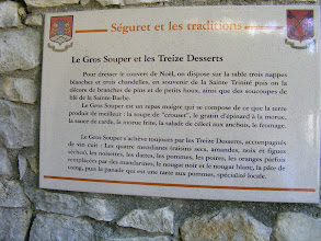 Photo: There are a number of historical plaques in the village, such as this one (loosely translated) describing the Christmas dinner and its 13 desserts. On the table are three white cloths and three candles, signifying the Holy Trinity, decorated with pine branches and holly, as well as saucers of Sainte-Barbe wheat. The dinner is a meatless meal of what the earth produces the best: soaked bread crust (we think), a gratin of spinach and cod, chard sauce, fried cod, a salad of celery and anchovies, and cheese. The dinner is always concluded by the 13 desserts: The four mendicant orders (raisins, almonds, nuts, and dried figs), hazelnuts,, dates, apples, pears, oranges occasionally replaced by mandarins, black nougat and white nougat, quince paste, then an apple tart, a local specialty.