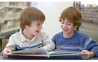 Two boys in library looking at book and laughing