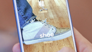 image of someone holding phone with shoe on the screen