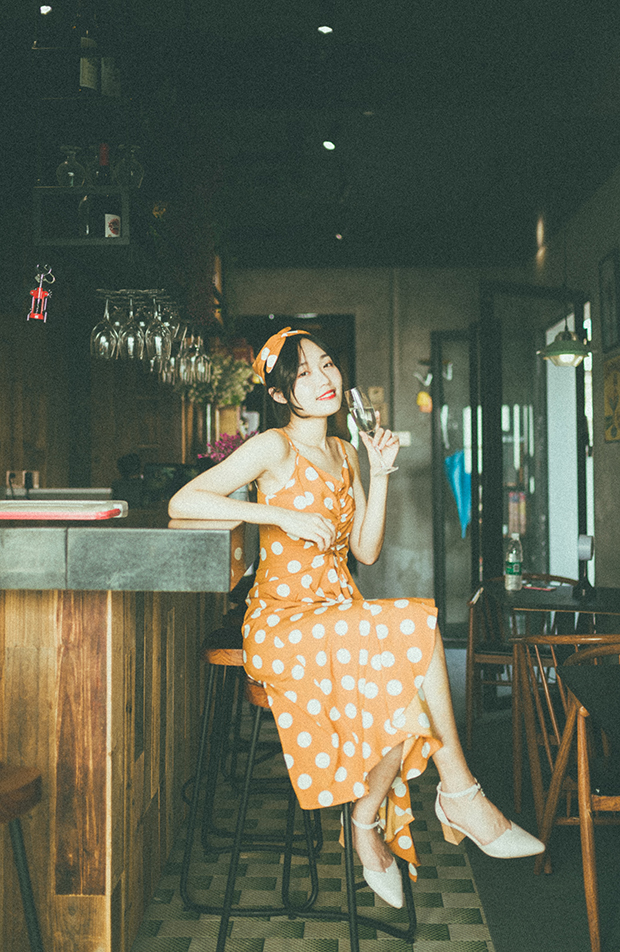 Woman sitting in an empty bar wearing an orange dress with white polka dots. She holds a glass of wine and is turned toward the camera, smiling