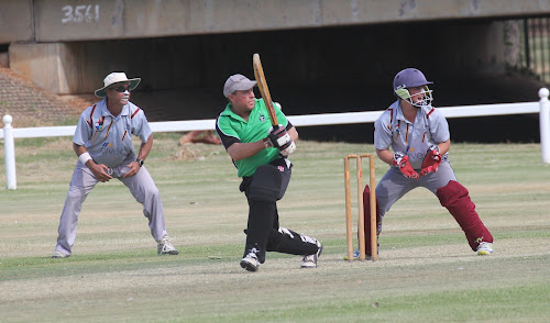 Crossroads' Glen Tomlinson, centre, drops down to one knee to smack one to the leg side boundary as Civeo slip Terry Baker and keeper Aaron Baker watch on.
