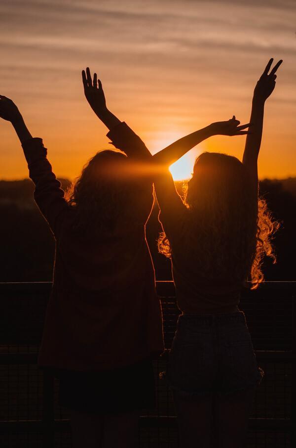 Foto de duas amigas com o por-do-sol ao fundo