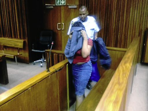 The 29-year-old woman found guilty of defeating the ends of justice over the rape of her child hides her face as she leaves the courtroom in the South Gauteng High Court in Johannesburg yesterday. / SUPPLIED