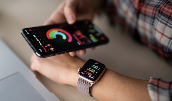 Wearable technology in healthcare: Man holding a smartphone and wearing a watch