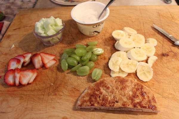 Yogurt, strawberries, bananas, grapes, and bread on a cutting board.