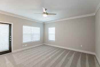 C1 living room with carpet, ceiling fan, and patio door