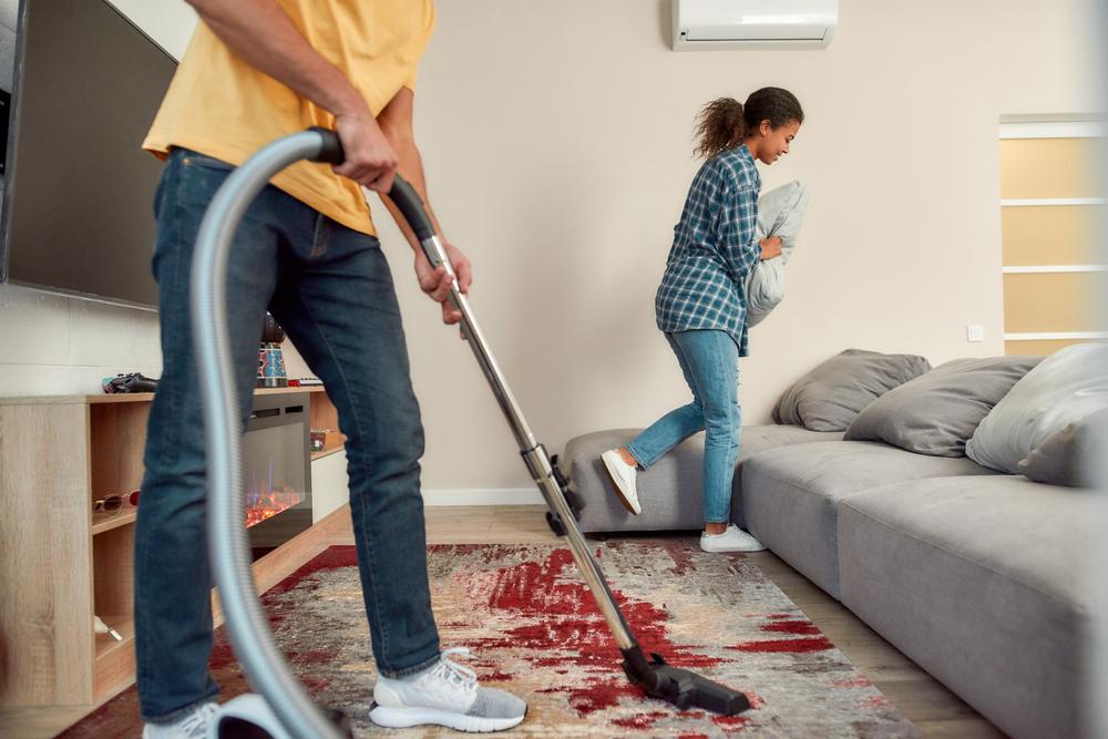 man vacuuming while woman fluffs pillow behind