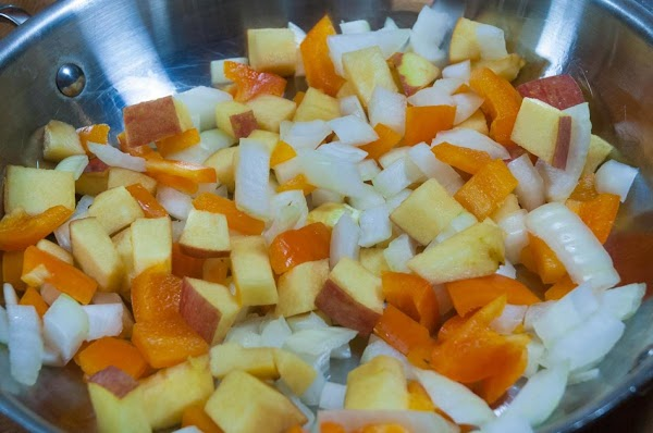 Add the onion, bell pepper, and apple to an ovenproof skillet with a lid.