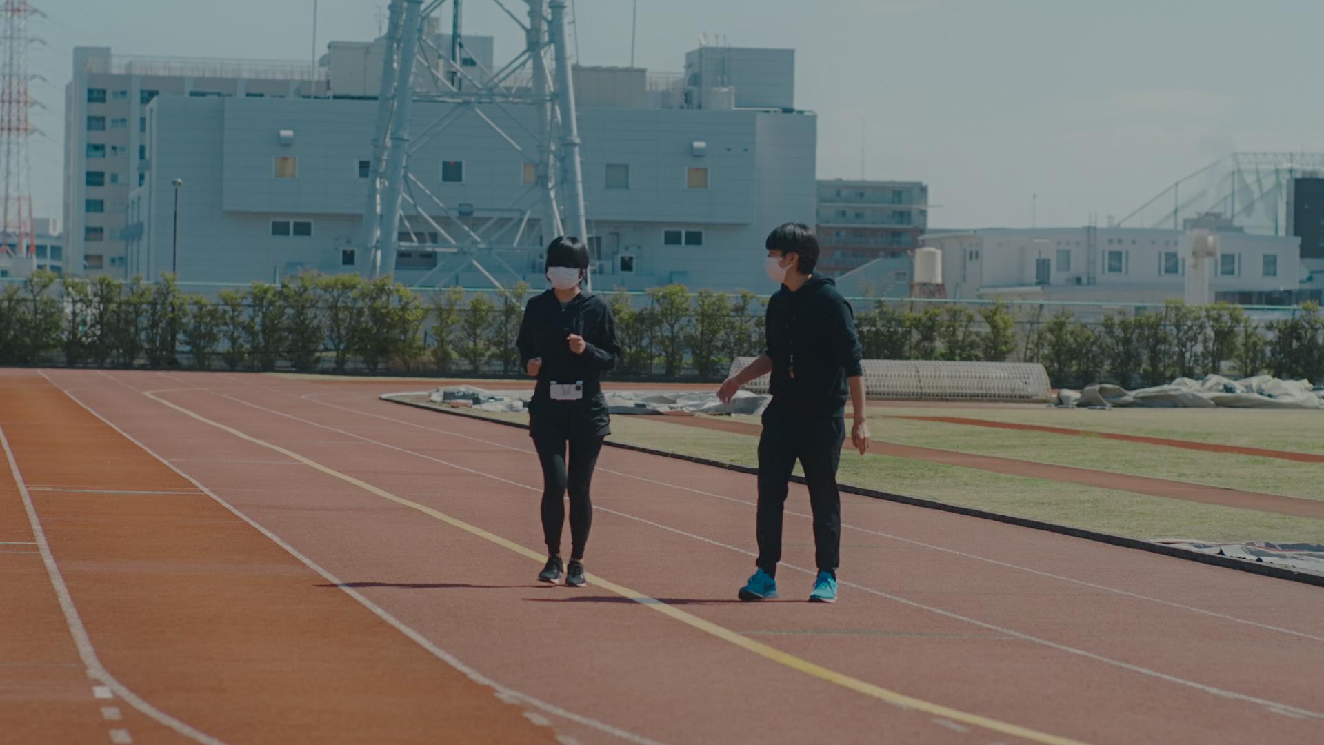 写真:アイマスクをした女性のテスト走者がガイドラインのテープにそって小走りする。