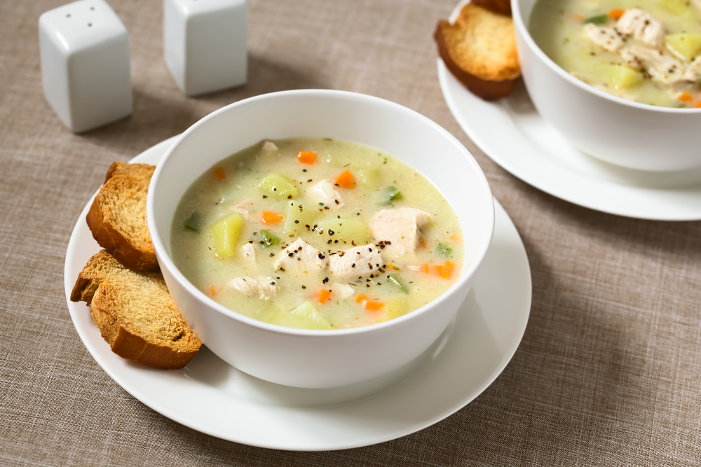 a bowl of potato soup on a plate with toast