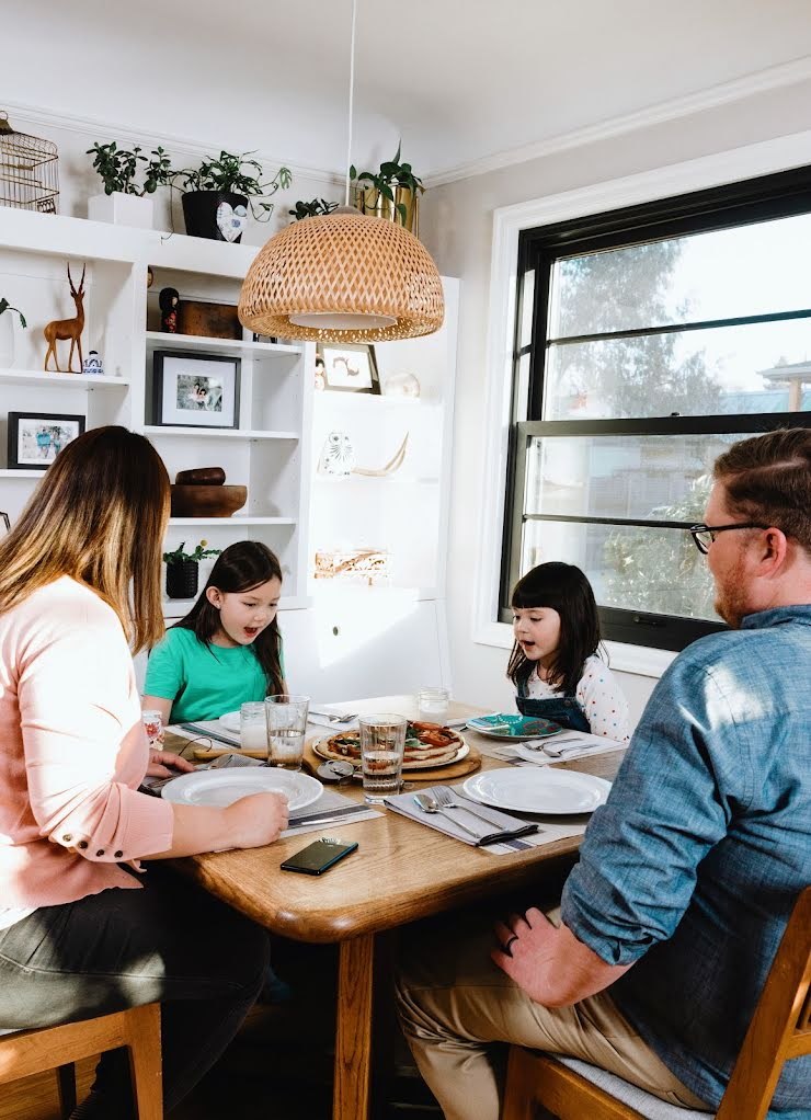 A mother, father, and their two daughters sit at a dining room table, a pizza in the middle, a phone in between the two parents.