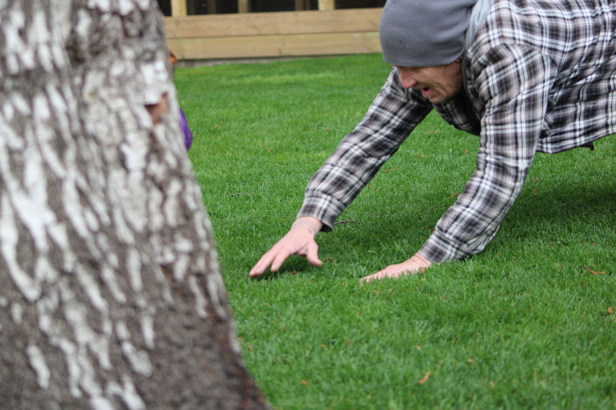 older-man-using-arms-to-break-fall-on-grass