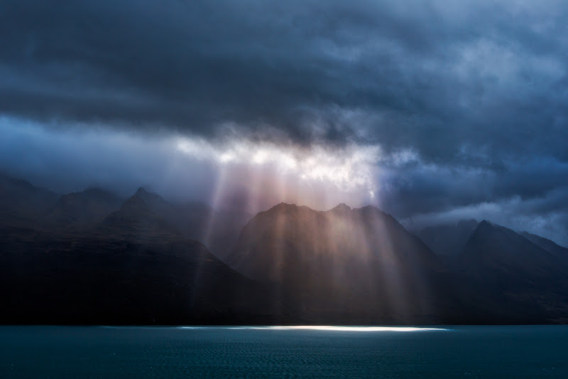 """Photo: """"Sun Streak"""" - Lake Wakatipu, New Zealand  As +Trey Ratcliffchauffeured +Karen Hutton, +Curtis Simmonsand I from Queenstown to Glenorchy, we stopped at many picturesque locations. This particular stop was a view of the sun streaking through some storm clouds onto Lake Wakatipu. Shortly after taking this picture, a strong wind storm rolled in, causing many trees and tree limbs to fall to the ground near Queenstown.  This is a single RAW file which I processed in Lightroom 4 and Photoshop CS6. I used Nik Viveza 2, Topaz Adjust, PhotoTools, and Color Efex Pro."""