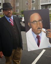 Photo: Kalonji holding paiting of Vivien Thomas done by local art student